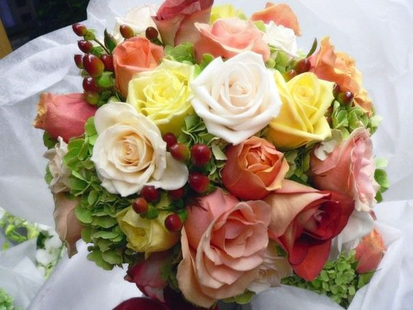 Clustered, hand tied bouquet of classic roses in shades of peach, cream, yellow paired with green...