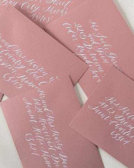 White calligraphy on dusty rose envelopes