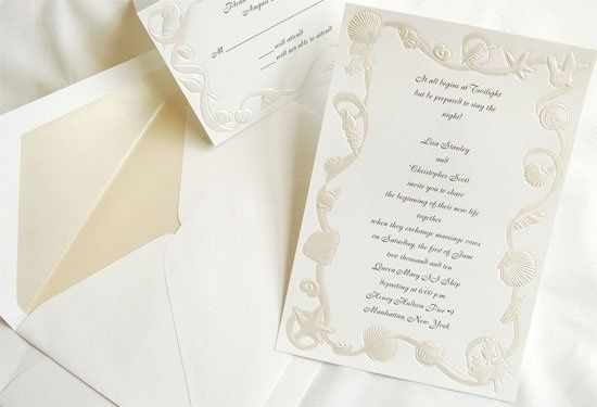 This radiant white, ocean themed wedding invitation features a beautiful frame of pearlized shells,...