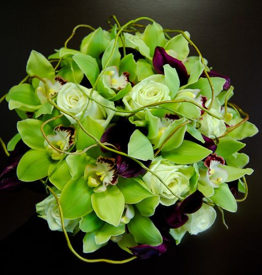 What an interesting combination of green  Cymbidium orchids, deep purple mini callas and ivory rose....