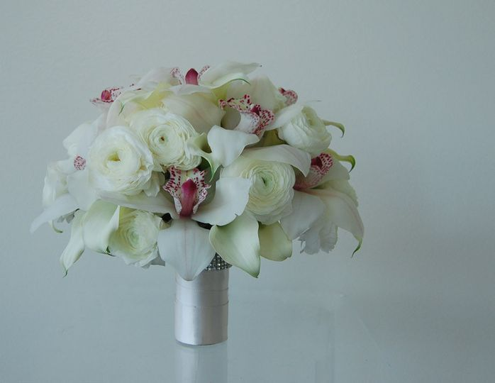 Simply elegant white bouquet with a kiss of blush pink. Cybidium orchids, ivory mini callas and lush...