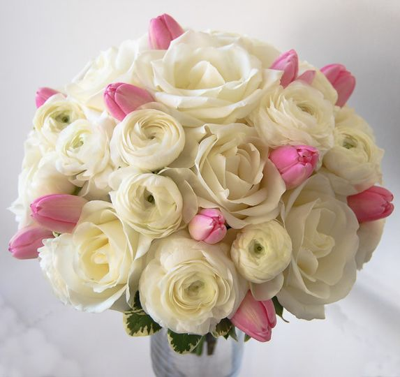 Predominantly white bouquet with touches of light pink tulips. A very sweet romantic and sweet...