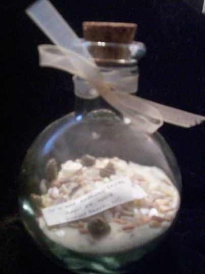 Layers of sand, crushed shells, and miniature shells. Message has bride and groom name with wedding...