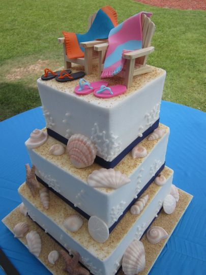 Beach themed wedding cake with seashells, flip flops and beach chairs on top.