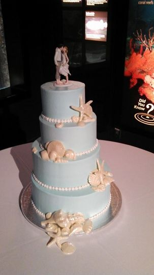 Wedding cake iced in buttercream with seashells made of white chocolate