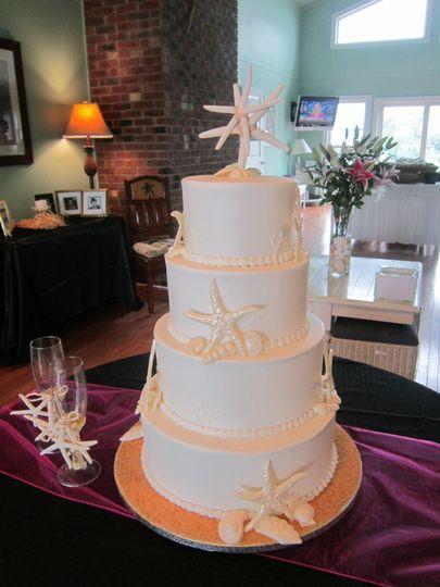 Starfish and seashells in white adorn this classy all white beach themed wedding cake.
