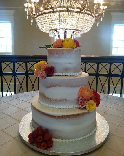 Semi naked cake with fresh flowers and raspberries for design.