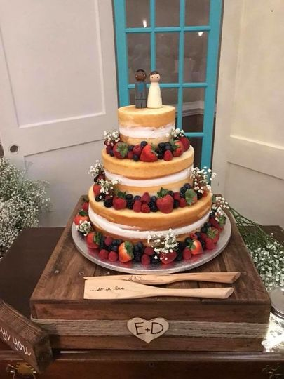 Naked wedding cake with an array of fresh fruits and baby's breath.