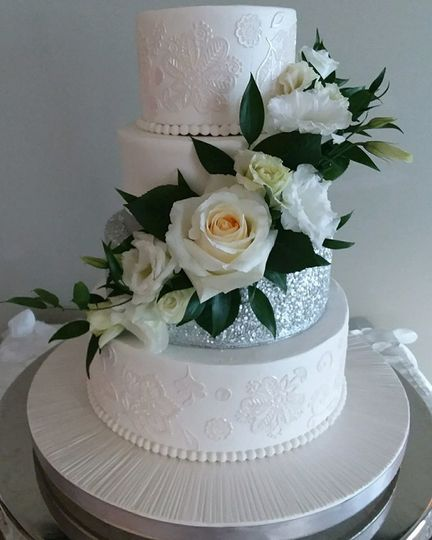 Wedding cake iced in buttercream with edible lace design, silver sequins and fresh flowers.
