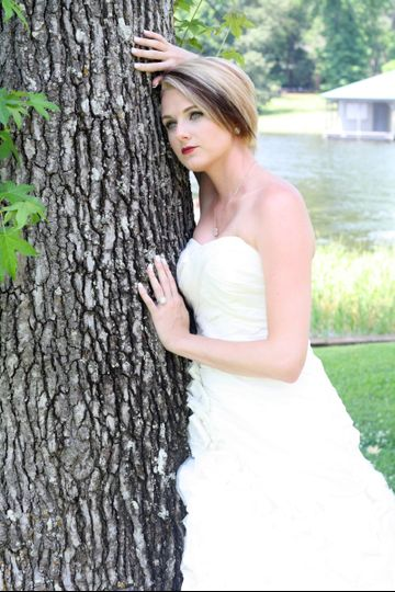 Bride posing beside a tree