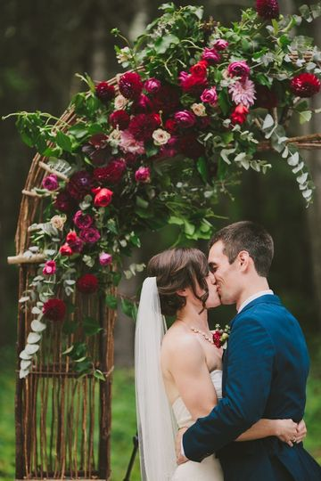 Couple kiss under rose decorated arch