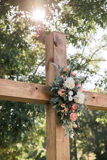 A wooden cross adorned with flowers