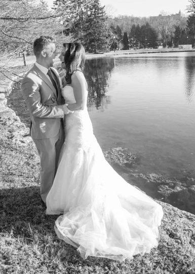 Bride and groom by lake black and whote