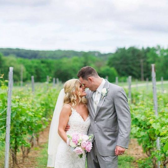 Newlyweds kissing in the vineyard