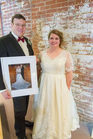 Restyled vintage gown. Groom is holding picture of the  dress as it was, originally. Photo by Little...