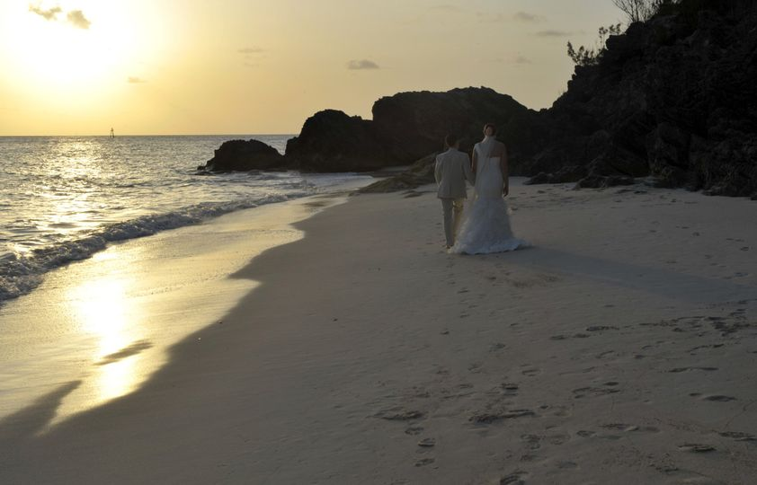 Newlyweds walk by the shore