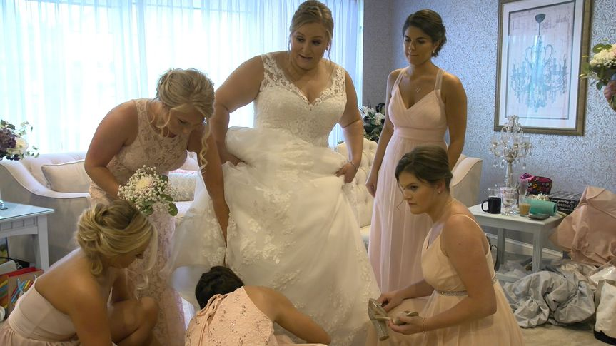 Bridesmaids helping with shoes