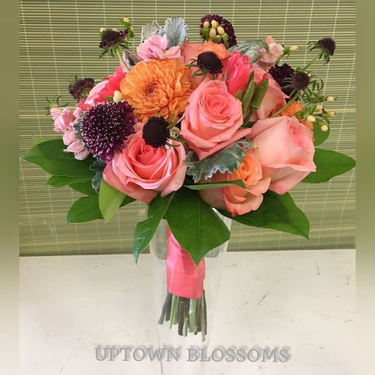 Bohemian style hand tied bouquet in coral tones with a deep highlight of Midnight Scabiosa.  Roses,...