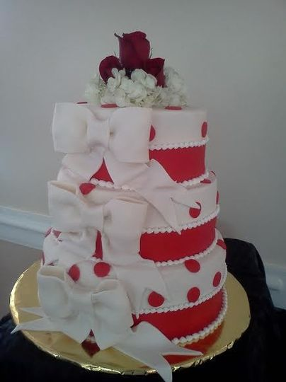 3-tier wedding cake with white ribbons and red details