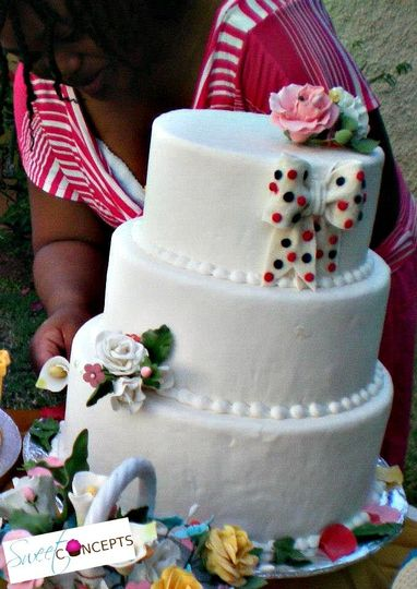 three tier wedding cake with ribbon and flowers