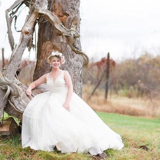 Bride sits by a tree