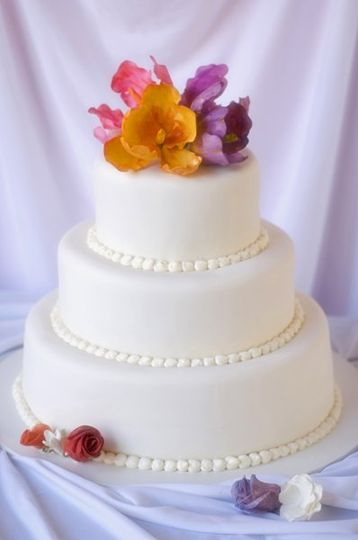 A classic white fondant wedding cake with hand-sculpted sugar tulips and roses.