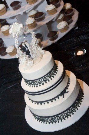 A beautiful ivory buttercream cake with black fondant ribbon, and lovely black fondant bow and...