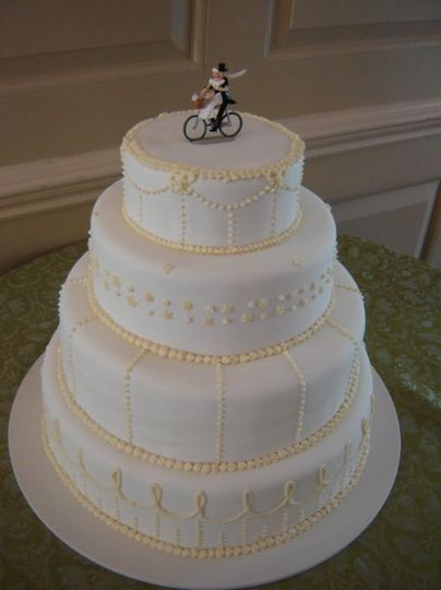 A gorgeous 4-tiered chocolate cake covered in white fondant with a petite dot pattern across each...