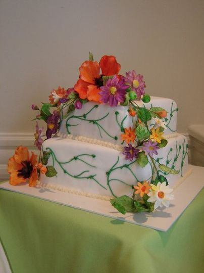A delicate square vanilla cake covered in smooth white fondant and green buttercream vines. The...