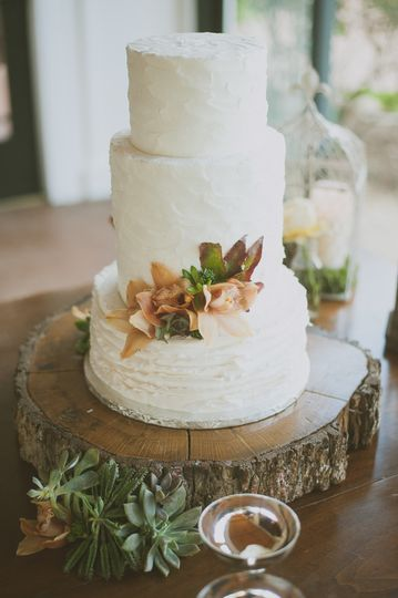 Simple white wedding cake with minimal flower design