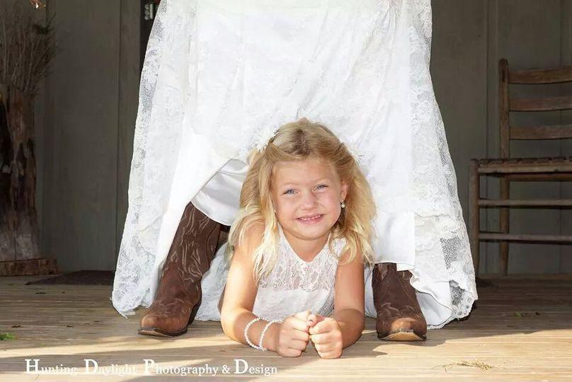 Flower girl hiding underneath the bride's dress