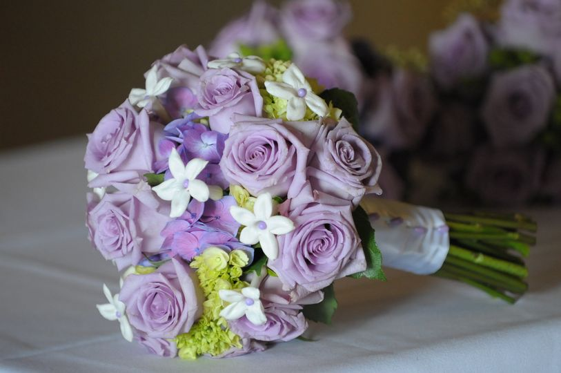 Hand tied bouquet of lavender roses, green hydrangea, and Stephanotis.