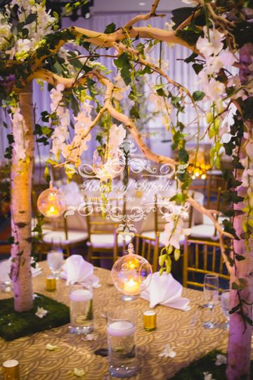 Family table with branches, crystals, candles, and floral arches