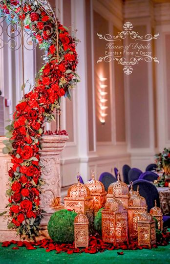 Column of cascading wild roses in plum and passionate red with antique lanterns decorated with wild...