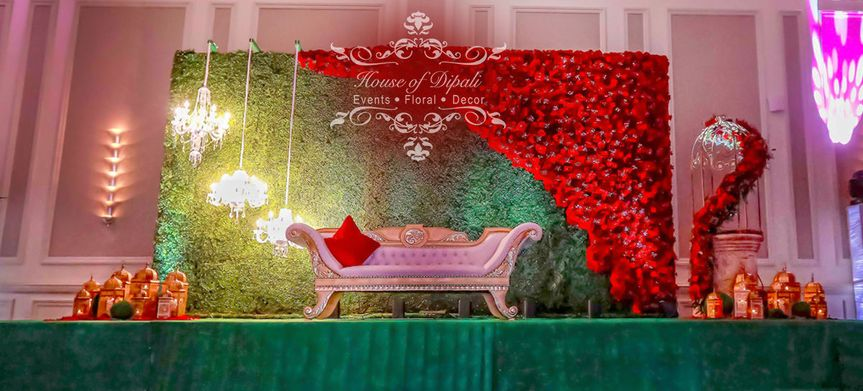 Bridal stage decorated with cascading wild roses in passionate red and beautiful greenery