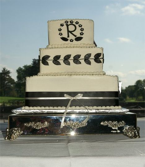This 3 tiered cake has a very modern look in a classic black and ivory look with  fondant leaves and...