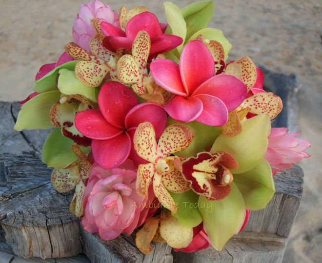 A tropical bouquet made of plumeria, cymbidium and mokara orchids, and pink ginger.
