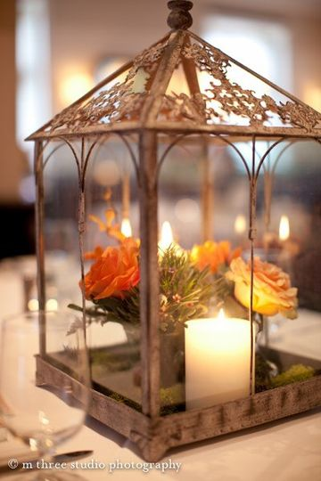 Flowers and candle in lantern centerpiece