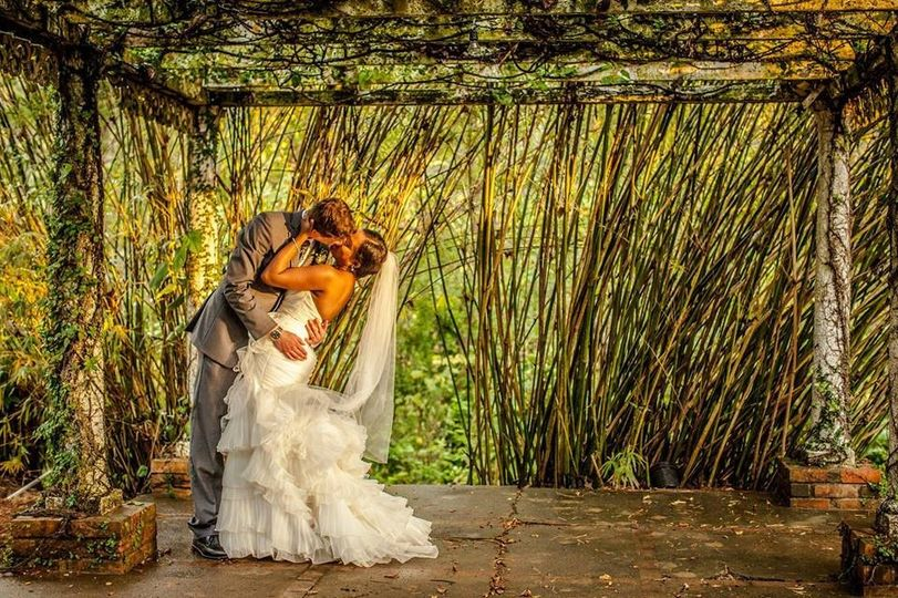 Bride and groom caught in intimate embrace under the bamboo trellis.