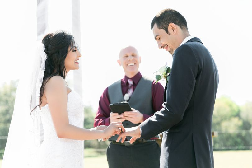 Bride puts on the ring on her groom