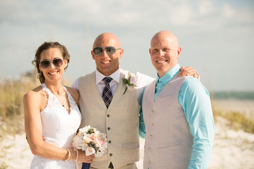 Officiant and the newlyweds at the beach