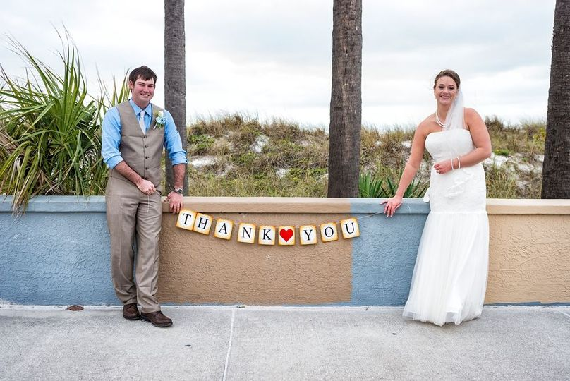 Groom and bride holding up the thank you sign