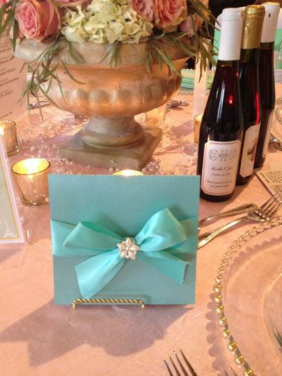 Lovely bi-fold in Tiffany blue with a satin bow and pearl and rhinestone embellishment