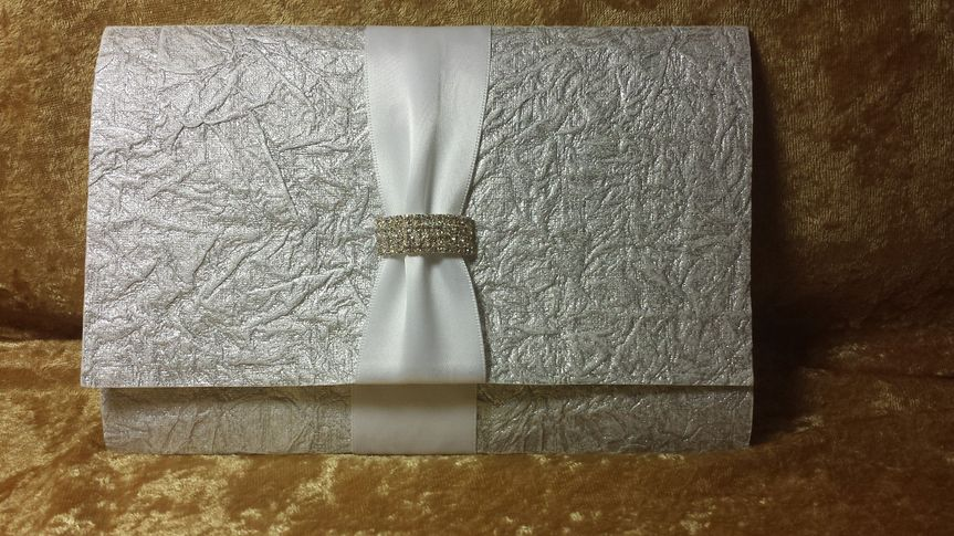 This silver crinkled paper from India with satin ribbon and large curved buckle is a tri-fold with a...
