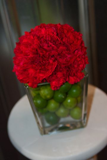Modern centerpiece of red carnations with a lime filled vase.