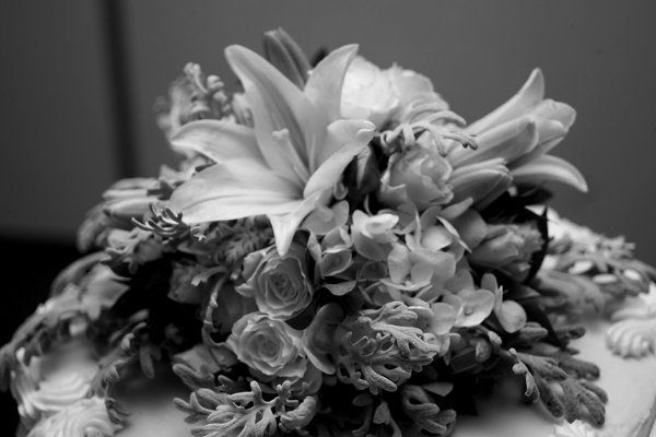 Cake topper of asiatic lilies, spray roses, hydrangea, and dusty miller.