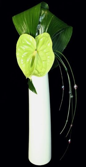 Green anthurium with ti leaves and bear grass with beads.