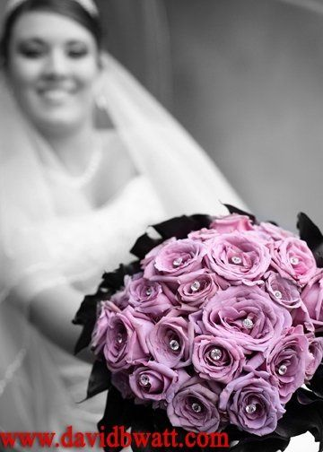 Lavender roses with diamond pins surrounded by dark purple calla lilies.
