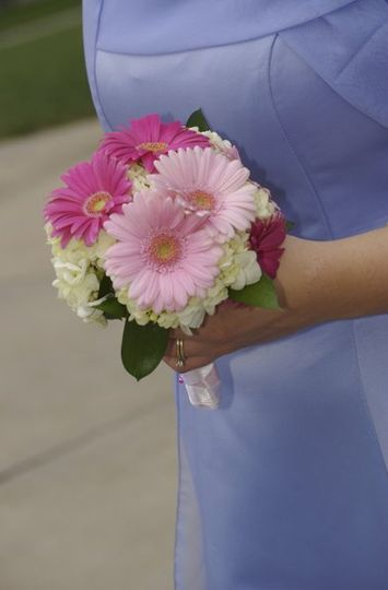 Two shades of pink gerbera daisies with white hydrangea and greens.