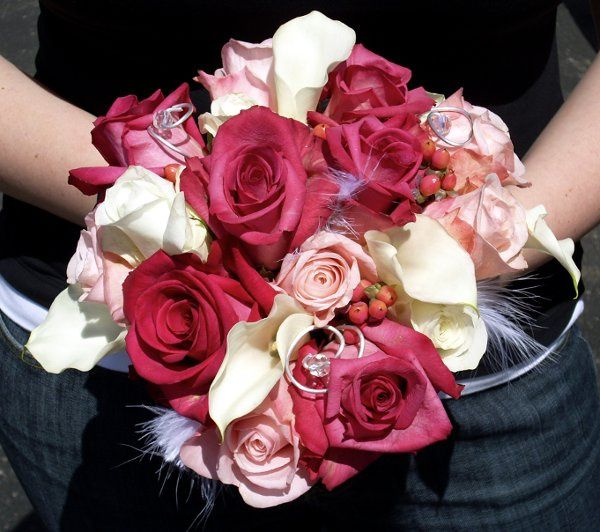 Funky bouquet of roses, calla lilies, and berries accented with wire curls and feathers.